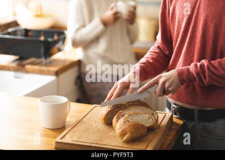 Man schneidet ein Laib Brot in der Küche - Stockfoto