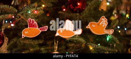 Essbar Weihnachten Dekoration - Vogel geformt Lebkuchen hängen an den Weihnachtsbaum mit Lichterkette und Glaskugeln - Stockfoto