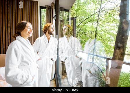 Junges Paar in Bademänteln stehen in der Nähe der Fenster mit schöner Aussicht auf den Wald im modernen Hotel Zimmer - Stockfoto