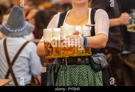 Oktoberfest, München, Deutschland. Frau Kellner mit traditionellen Kostüm holding Biere - Stockfoto