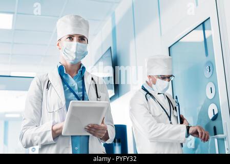 Low Angle View der weiblichen Arzt in medizinischen Maske mit digitalen tablet, während ihre männlichen Kollegen hinter mit Zwischenablage im Krankenhaus Flur - Stockfoto