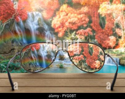 Konzeptionelle Bild der Wasserfall in Brillen Kontaktlinsen konzentriert über das Foto der schönen Wasserfall mit Soft Focus und Der Regenbogen im Wald verschwommen - Stockfoto