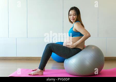 Portrait von asiatischen Schwangere Übung im Sport Zimmer tun, sitzen auf den großen Ball, gesunde Mutterschaft Konzept - Stockfoto