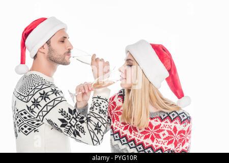 Paar in Pullover und Santa Claus Hüte trinken Champagner isoliert auf weißem - Stockfoto