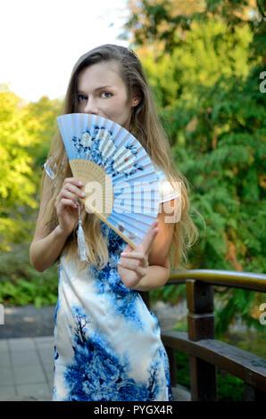 Weibliche Model aus Polen tragen traditionelle chinesische Kleidung, hält das Gebläse. Frau posiert im asiatischen Stil. - Stockfoto