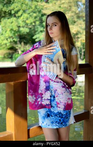 Weibliche Model aus Polen tragen traditionelle chinesische Kleidung in blauer Farbe mit bunten Schal. Frau posiert im asiatischen Stil. - Stockfoto