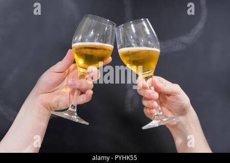 Zwei Freunde Toasten mit Gläser Bier in der Kneipe. Blackboard Hintergrund. - Stockfoto