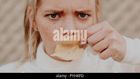 Junge Frau mit Sommersprossen in ihrem Gesicht runzelte die Stirn und die Abdeckung der Mund mit einem Blatt