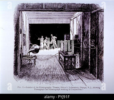 Eine marode Teerpappe shack in East Orange, NJ, im Besitz von Thomas Edison, ist der erste Motion Picture Studio in den Vereinigten Staaten. Auf der Bühne ist ein Kellner neben einem Mann an einem Tisch sitzen, während ein anderer Mann steht. Mit Blick auf die Männer ist eine Holz- Kamera, amtlich kinetograph (Edison nannte es der Hundehütte). - Stockfoto