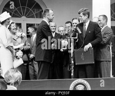 Astronaut Alan B. Shepard, Jr. erhält die NASA Distinguished Service Award von United States Präsident John F. Kennedy Mai 8, 1961, Tage nach seiner Geschichte, Herr-3 Flug. Shepard's Frau und Mutter auf der linken und die anderen sechs Mercury Astronauten sind im Hintergrund. - Stockfoto