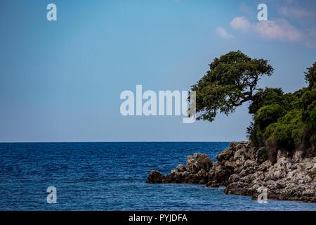 Feder tagsüber schönen Ionischen Meer mit klaren türkisfarbenen Wasser, Felsen und Bäume Küste Blick von Ksamil Strand, Albanien. Tief blauen Himmel mit weißen Wolken. - Stockfoto