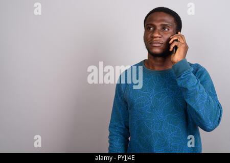 Junge afrikanische Mann mit Handy vor grauem Hintergrund - Stockfoto