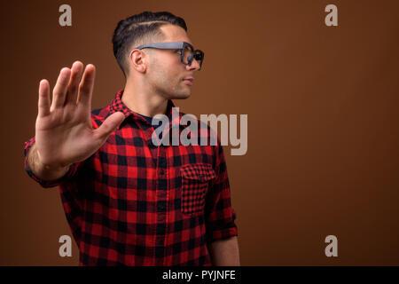 Porträt der jungen gutaussehenden Mann gegen braunen Hintergrund - Stockfoto