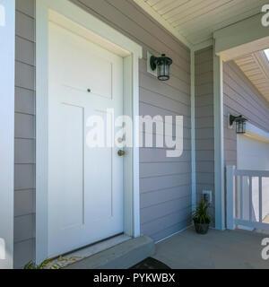 Weiße Eingangstür eines Haus mit Veranda und Garage - Stockfoto