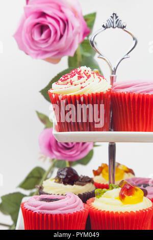 Studio geschossen von bunt geschmückten Cupcakes auf Kuchen stand mit rosa Rosen hinter sich. - Stockfoto