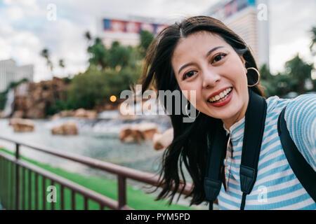 Süße Dame unter selfie vor der Teich im Park in Amerika. Junge Mädchen unabhängige Reisen in Las Vegas. Frau aufnehmen portrairt Foto con