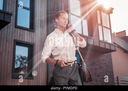 Ansprechende stilvollen Mann mit Tattoo auf seiner Hand Gefühl besetzt auf dem Weg zum Büro - Stockfoto