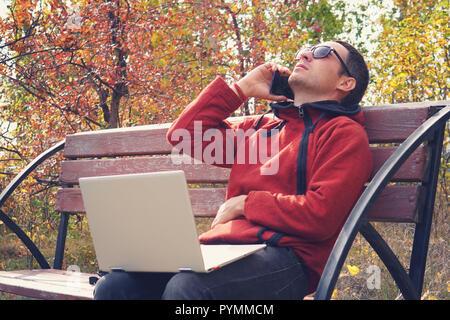 Beschäftigte Person arbeitet online außerhalb der im Urlaub. junger Mann Arbeiten am Laptop Computer in legere Kleidung. Auf dem Smartphone sprechen, sitzt im Park. s - Stockfoto