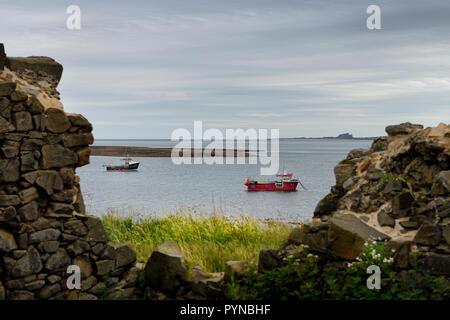 Zwei Fischerboote bei Ebbe im Hafen der heiligen Insel von Lindisfarne mit Bamburgh Castle durch die Stahl Ende Ruinen England Großbritannien - Stockfoto