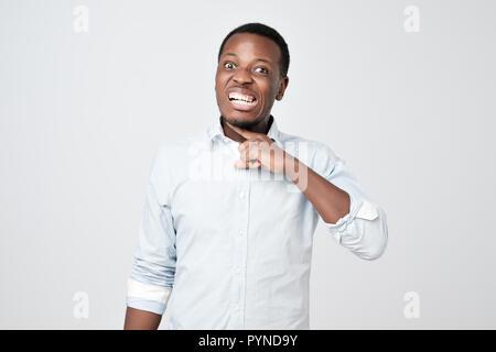 Afrikanischer mann Grimassen von Zorn, die Finger in der Nähe von Hals, imitiert Messer, schneiden Kehle - Stockfoto