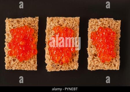 Drei Sandwiches, Kanapees mit natürlichen roter Lachskaviar auf einem dunklen Kammer, Ansicht von oben - Stockfoto