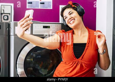 Freundliche nette hübsche junge Dame mit schwarzem Haar hören Musik mit Kopfhörer während der Einnahme von selfie mit dem Telefon. Waschen machin im Hintergrund, - Stockfoto