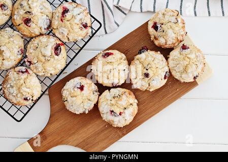 Frische cranberry Muffins Kühlung auf Bäcker Zahnstange und ein Holz Schneidebrett über eine rustikale weißem Hintergrund. Bild geschossen von oben mit freier Speicherplatz - Stockfoto