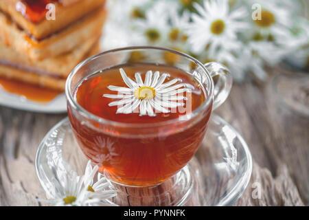 Eine klare Schale von Arzneimitteln Kamille Tee auf einem alten Holztisch. Gesundheit und gesunder Lebensstil Konzept - Stockfoto