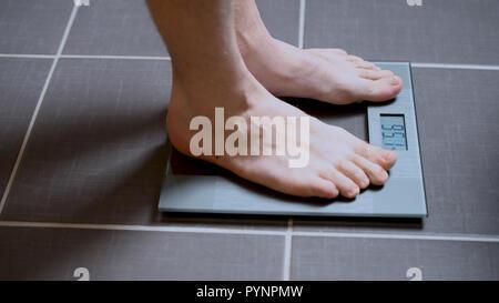 Männliche Füße auf Glasmaßstäbe, Diät, Gewicht, Nahaufnahme, Mann, der auf der Skala - Stockfoto
