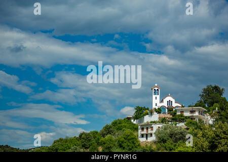 Feder tagsüber Landschaft mit Christlich-orthodoxen Kirche im Dorf der Mursi, Albanien. Landschaft bewölkten Himmel mit Gebäude auf der grünen Hügel - Stockfoto