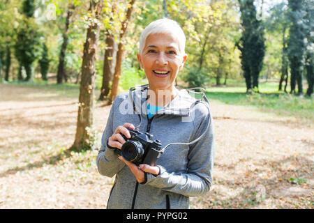 Portrait von charmanten älteren Frau mit retro Kamera zum Foto im Wald bereit.