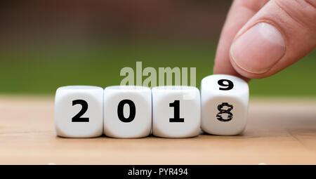 Hand dreht einen Würfel und symbolisch Veränderungen der Jahre 2018 bis 2019 - Stockfoto