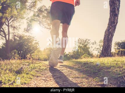 Rückansicht der Sport Menschen mit zerrissenen sportlichen und muskulösen Beine, die Straße in der Natur im Herbst Sonnenuntergang in joggen Training Training in die Landschaft i - Stockfoto