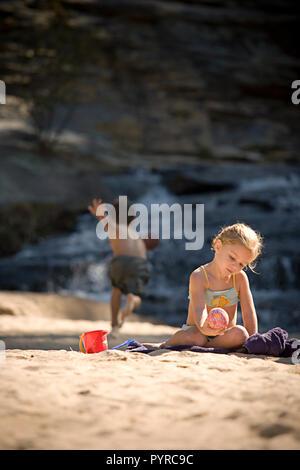 Kleine Mädchen spielen im Sand mit Junge laufen für Ball im Hintergrund - Stockfoto