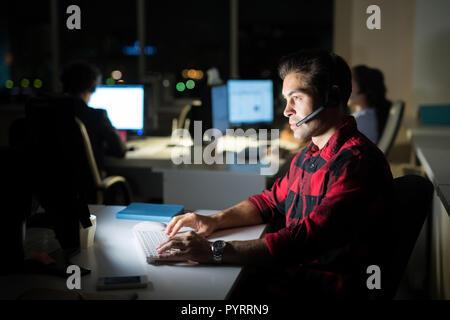 Help Desk Operator Arbeiten bei Nacht Stockfoto