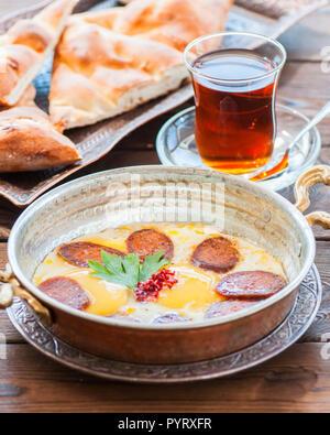 Türkisches Frühstück - Spiegeleier mit Würstchen (sucuk) und Gewürzen in einer Pfanne, Glas Tee auf einem hölzernen Hintergrund. - Stockfoto