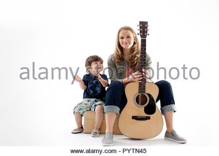Portrait von Mitte der erwachsenen Frau mit Gitarre zwischen ihre Beine und ihr kleiner Sohn klatschen neben ihr sitzen. - Stockfoto