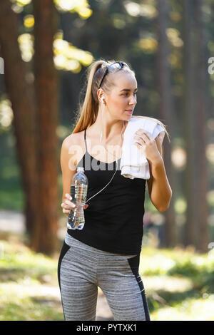 Müde junge athletische Frau mit Handtuch ruhen unter den Bäumen im Park nach Morgen laufen und Trinkwasser, gesunden Lebensstil und Personen Konzept - Stockfoto