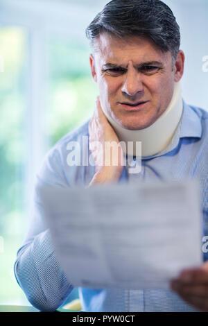 Reifer Mann Lesen Schreiben nach Erhalt die Nackenschmerzen - Stockfoto