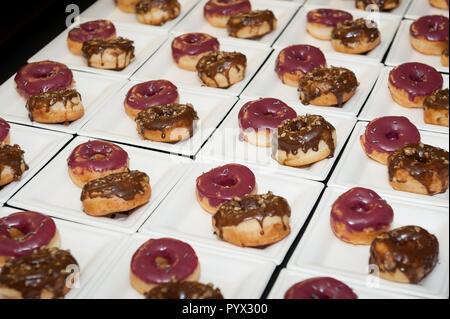 Mehrere Platten mit jeweils zwei frosted Donuts (Donuts). - Stockfoto