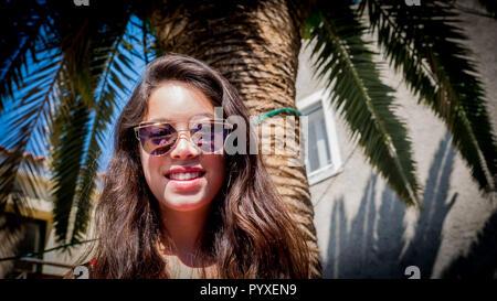 Nahaufnahme von Teen lächelnd vor Palm Tree - Stockfoto