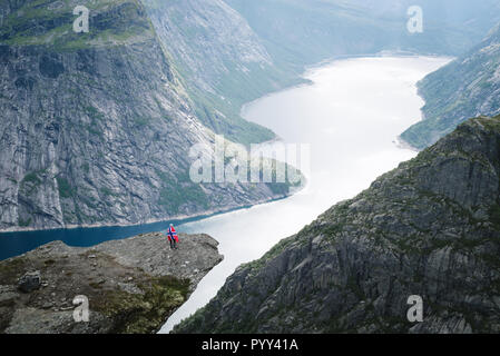 Trolltunga Wandern. Ringedalsvatnet - See in der Gemeinde Odda in Hordaland County, Norwegen. Mädchen mit norwegischer Flagge - Stockfoto