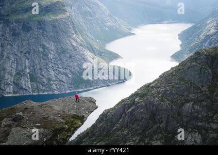 Trolltunga - Klippe Fels über dem Ringedalsvatnet in Norwegen. Mädchen tourist genießt eine wunderschöne Aussicht - Stockfoto