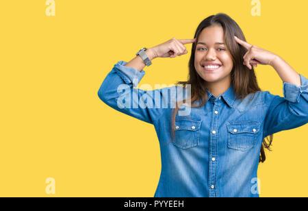 Junge schöne Brünette Frau mit Blue Denim shirt über isolierte Hintergrund Lächeln zeigte mit beiden Händen, Finger, große Idee zu Kopf oder wenn - Stockfoto