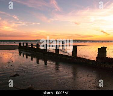 Paar bei einem Spaziergang auf dem Sand hinter einem hölzernen Strand buhnen am Strand bei Sonnenuntergang - Stockfoto