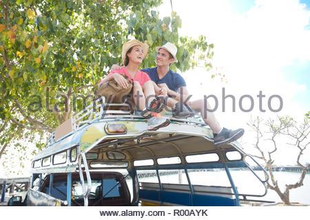 Junges Paar auf Tour Bus Dach sitzt - Stockfoto