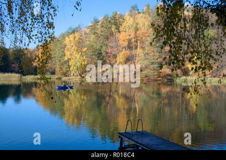 Schönen herbstlichen Wald spiegelt sich in den ruhigen Wassern des Sees, mit einem Fischer in einem blauen Boot - Stockfoto