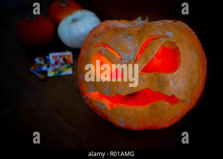 Eine gruselige Jack O Lantern mit Pumkins und Süßigkeiten im Hintergrund - Stockfoto