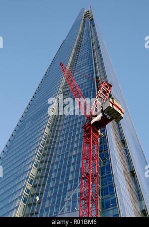 Der Shard, Großbritanniens größte Gebäude, in der Nähe vom Boden aus gesehen, mit zwei sehr groß rot lackierten Turmdrehkrane im Vordergrund. - Stockfoto