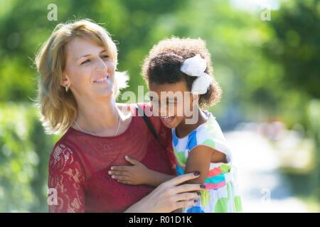 Einer Frau mit einem fördern - Kind in ihren Armen erstellt eine glückliche Familie. - Stockfoto
